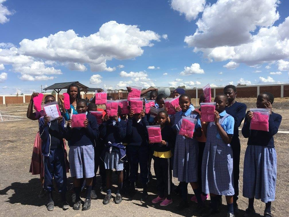 Schoolgirls presenting their donated safe pads